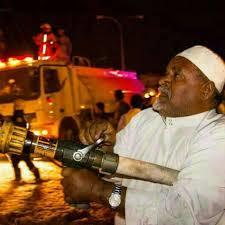 """صورة """"متقاعد"""" يساعد زملائه في إخماد حريق"""