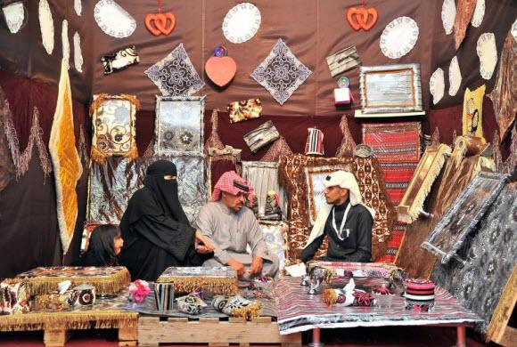 مواطن يدعم زوجته في تسويق إبداعاتها بمهرجان الزيتون بالجوف