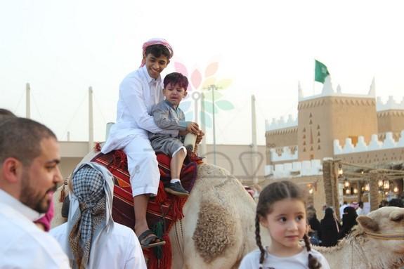 بالصور ..تجربة ركوب الإبل تستهوي أطفال الجنادرية