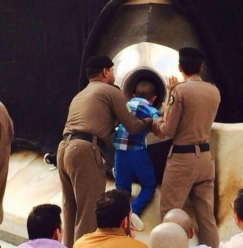 بالصورة.. رجلا أمن بالحرم يحملان طفلاً معاقاً محققين أمنيته بتقبيل الحجر الأسود